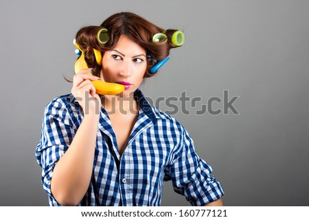 girl holding banana like cell phone - stock photo