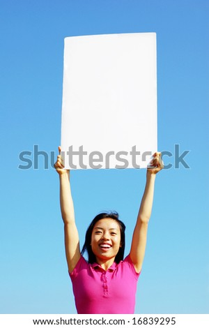 Girl holding blank sign in front of big blue sky.