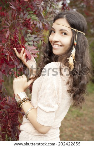 Girl holding branches of red leaves, enjoying fall