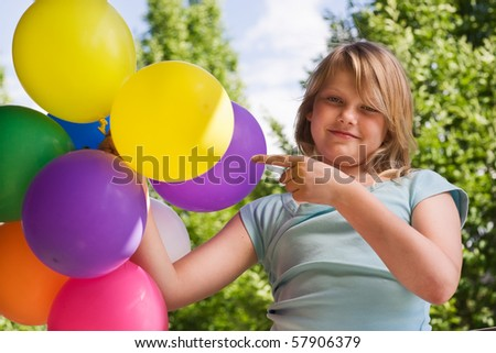 Girl holding bunch of balloons - stock photo