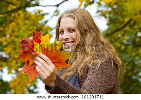 Girl holding colorful maple leaves