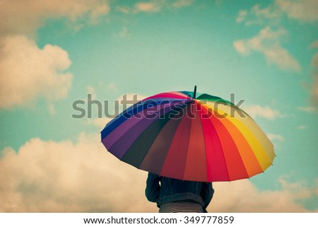 Girl holding colorful rainbow umbrella up to the sky, grunge vintage filter. - stock photo