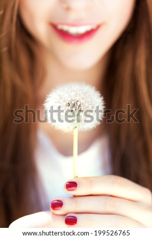 Girl holding dandelion - stock photo