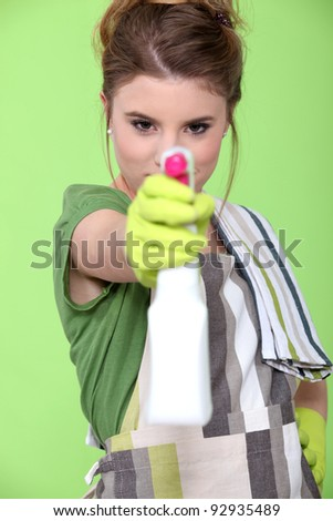 girl holding detergent with pistol pump against green background - stock photo
