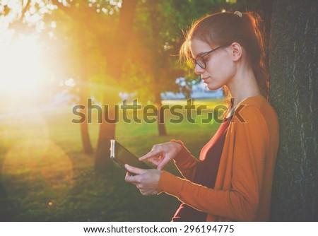 girl holding digital tablet pc at park in summer sunset light - stock photo