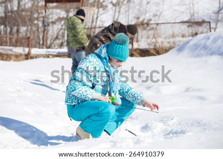girl holding fishing pole and drop fishing line into  hole in winter - stock photo