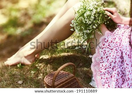 Girl holding flowers in her lap - stock photo