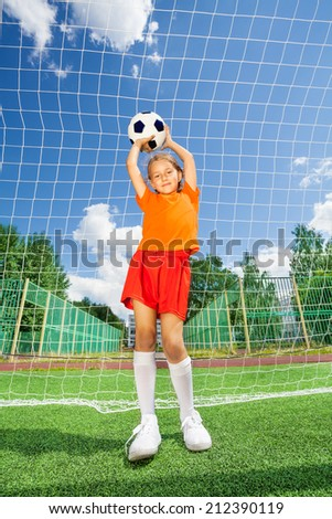 Girl holding football on both straight arms - stock photo
