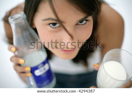 girl holding glass of milk and bottle - stock photo