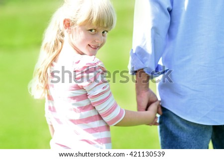 Girl holding hands with her father outside - stock photo