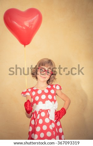 Girl holding heart shape red balloon. Valentine's day concept