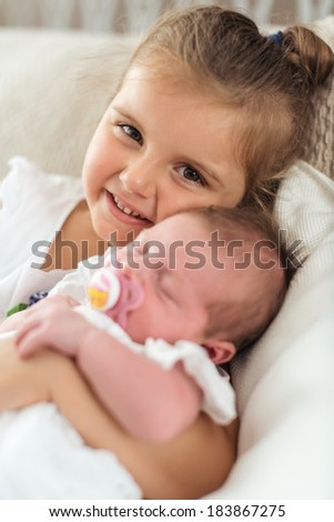 girl holding her newborn sibbling - stock photo