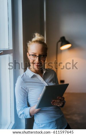 Girl holding her tablet watching through a window