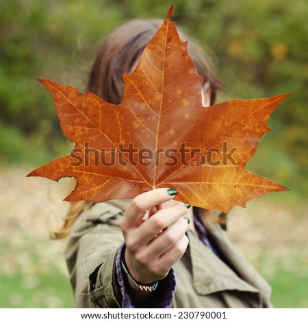 Girl holding leaf, Girl holding planetree leaf in the front of her face - stock photo