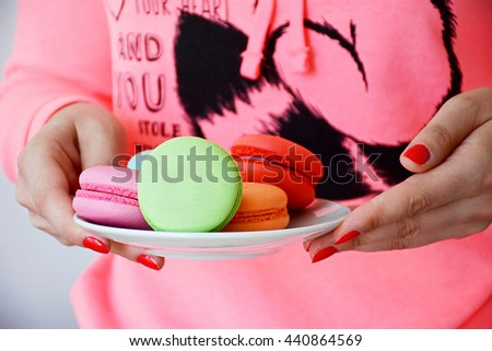 Girl holding macaroons. Colorful various macaroons on a plate in girls hands with red nails.