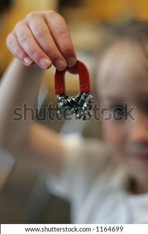 Girl holding magnet - stock photo