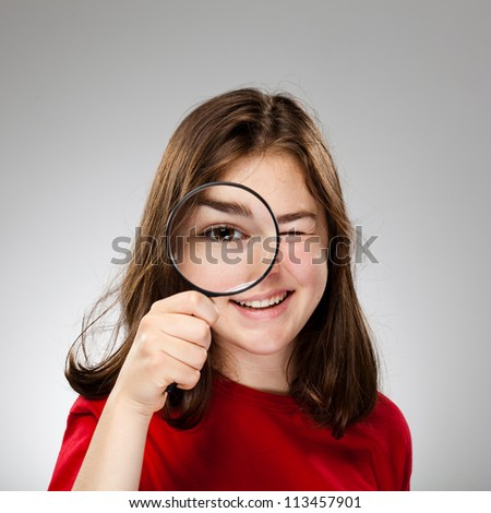 Girl holding magnifying glass on gray background - stock photo
