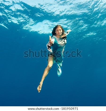 Girl holding out her hand underwater. - stock photo