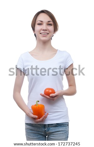 Girl holding pepper and tomato in the hands isolated on white - stock photo