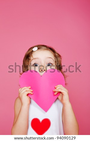 Girl holding pink paper heart in hands - stock photo