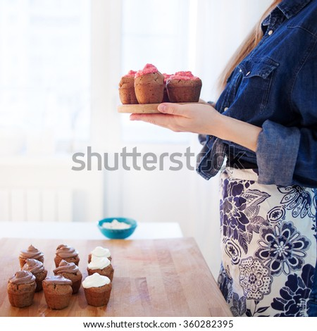 girl holding plate of fresh hot muffins, blurred background - stock photo