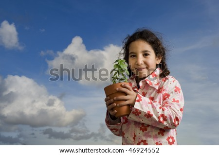 girl holding potted plant against cloudy sky