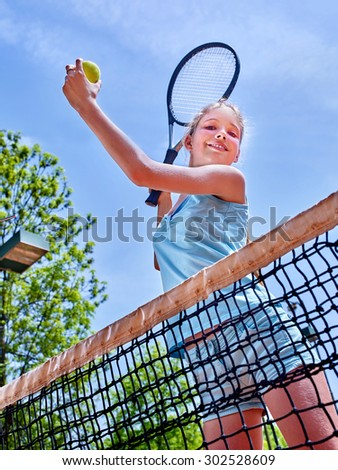 Girl holding  racket and ball on  brown tennis court. - stock photo