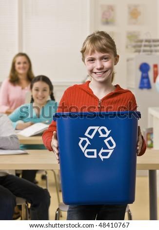 Girl holding recycling bin - stock photo