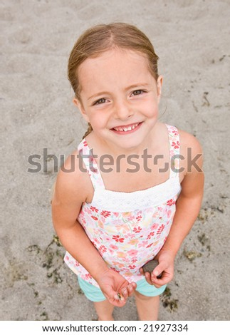 Girl holding rocks at beach - stock photo