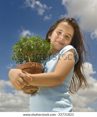 girl holding small tree against cloudy blue sky - stock photo