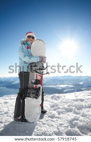Girl holding snowboard on top of mountain, blue sky background