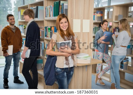 Girl holding tablet with group of students in college library
