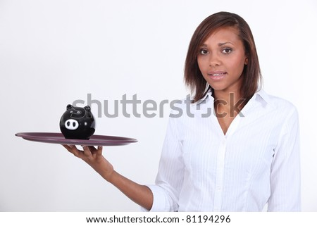 Girl holding tray with piggy bank - stock photo