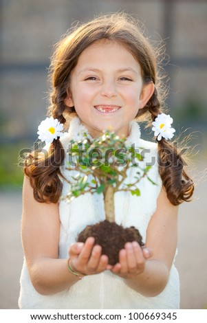 girl holding tree as environmental or nature concept ( focus on child ) - stock photo