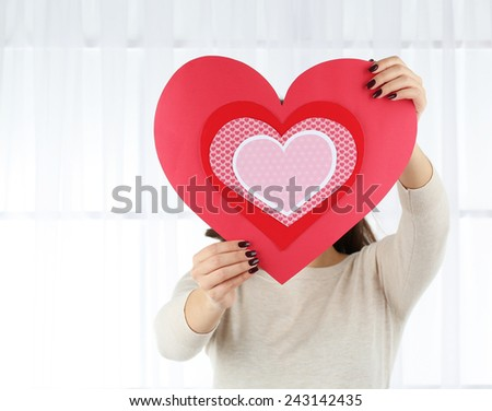 Girl holding Valentine card on bright background