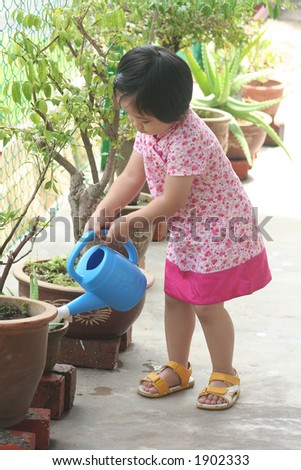 Girl holding watering-can & watering plant - stock photo