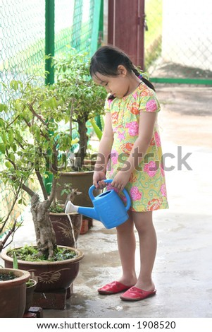 Girl holding watering-can watering the plant - stock photo
