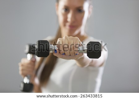Girl holding weights in her hands - stock photo