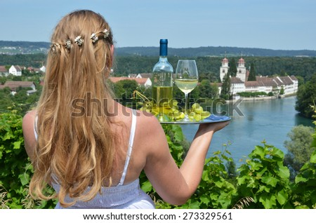 Girl holding wine and grapes on the plate. Vineyards of Rheinau, Switzerland - stock photo