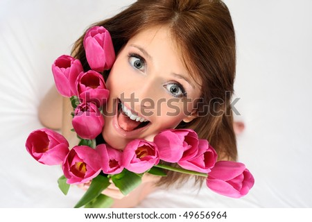 Girl holds a bouquet of tulip looking up - stock photo