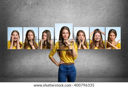 Girl holds and changes her face portraits with different emotions - stock photo