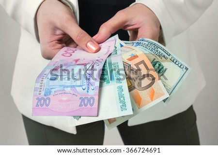 Girl holds banknotes of different countries. Close up, wide angle