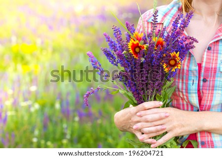 girl holds bouquet of  salvia and camomile