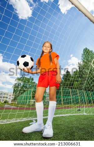 Girl holds football, stands in front of  woodwork - stock photo