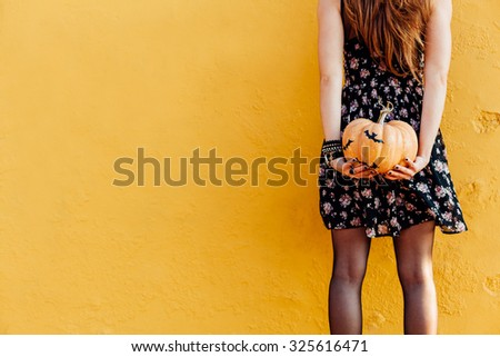 Girl holds Halloween pumpkin with bats concept and copy space - stock photo