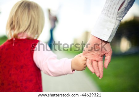 girl holds her mother by hand - stock photo
