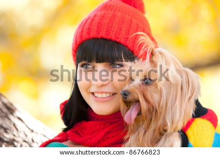girl holds small dog in hands