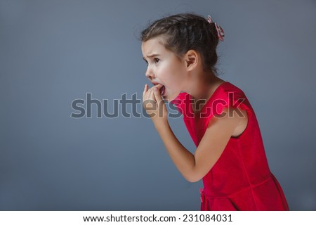 girl holds the hand of a child vomits in his mouth on gray background - stock photo