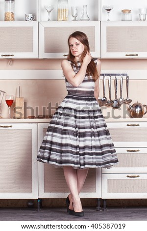 Girl hostess looks at the pan as if in a mirror. She's in the kitchen.