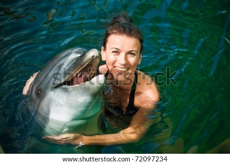 Girl hugging a dolphin in the water - stock photo